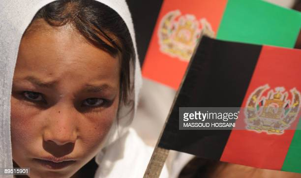 A Afghan ethnic Hazara girl holds a national flag at a campaign event for President Hamid Karzai one of 41 presidential candidates in PetabeShinia...