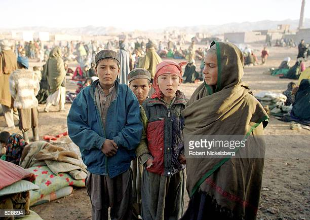 Afghan families stand outside after sleeping in nearly freezing temperatures without shelter February 23 2001 at the Minarets refugee camp in Herat...
