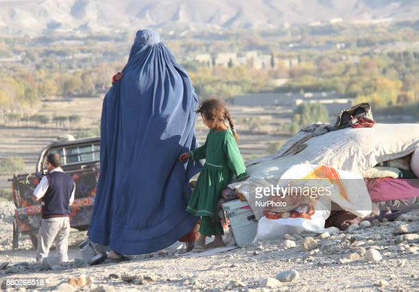 Afghan families who have been displaced due to conflicts between Taliban militants and Islamic State take shelters on the outskirts of Khogiyani...