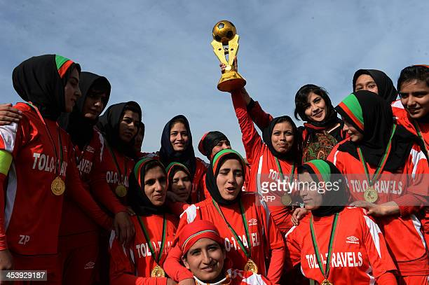 Afghan female football players from Afghan team celebrate with the trophy after their women's football tournament final match against Isteghlal in...