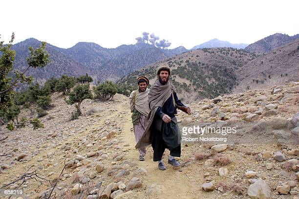 Afghan fighters from the eastern alliance walk away following a cluster bomb being dropped on Al Qaeda positions December 14, 2001 in the Tora Bora...
