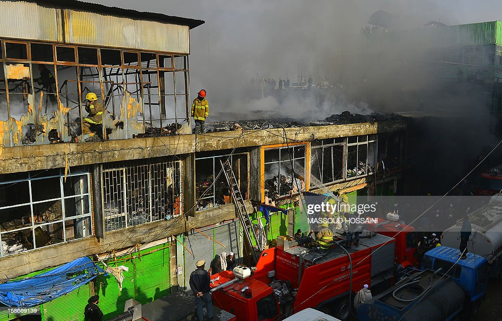 Afghan firefighters attempt to control a fire that swept through a market in Kabul on December 23, 2012. A huge fire swept through a market in downtown Kabul on December 23, destroying hundreds of shops and forcing the city's nearby money exchange to evacuate, police and witnesses said. There were no reports of any casualties in the early morning blaze which destroyed most of the cloth market's 500 shops, Kabul fire department officials told AFP. AFP PHOTO/ Massoud HOSSAINI