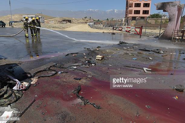 TOPSHOT Afghan firefighters wash the road at the scene of a suicide bomb attack in Paghman district in Kabul on May 25 2016 Ten people were killed in...
