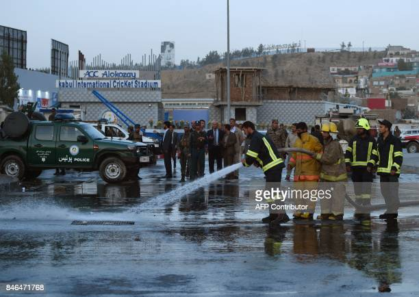 Afghan firefighters work at the site of a suicide bomb attack near the Kabul International Cricket ground in Kabul on September 13 2017 A suicide...