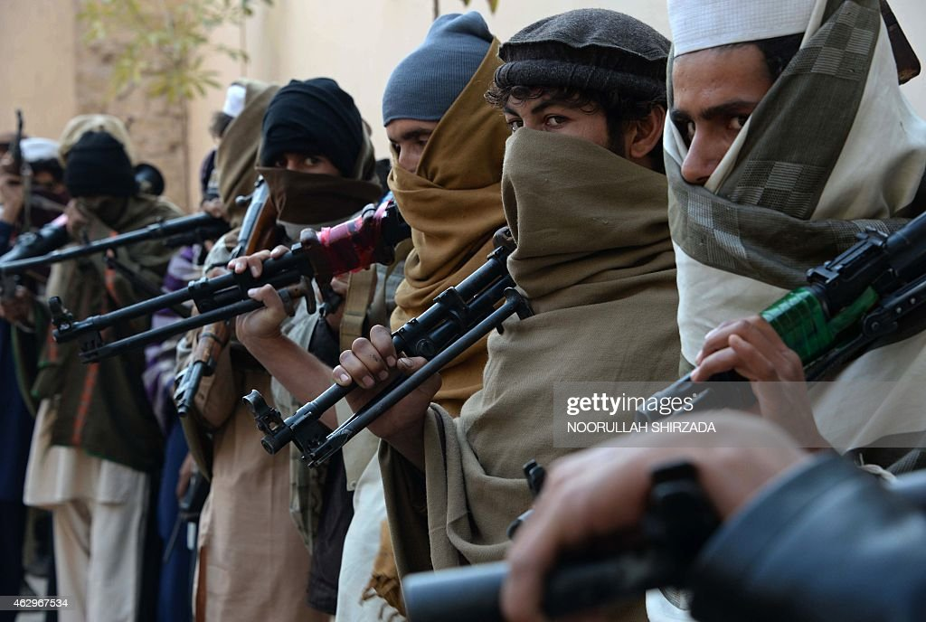 Afghan former Taliban fighters are photographed holding weapons before they hand them over as part of a government peace and reconciliation process at a ceremony in Jalalabad on February 8, 2015. Over twenty former Taliban fighters from Achin district of Nangarhar province handed over weapons as part of a peace reconciliation program. AFP PHOTO / Noorullah Shirzada