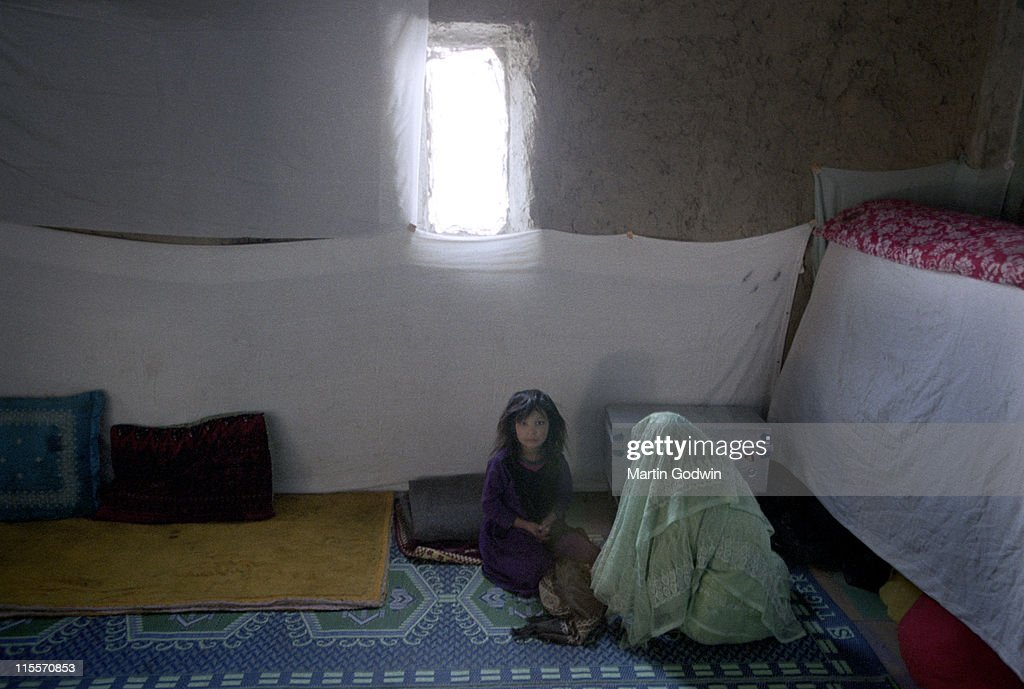 Afghan Girl In Her Bedroom, With Her Sister In Green Veil, Sitting On Rugs