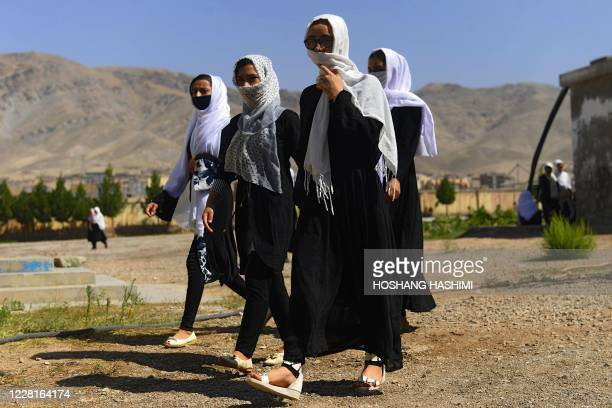 Afghan girl students cover their faces with scarfs as they walk inside the compound of their school after it was reopened, which was earlier closed...