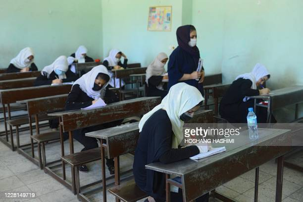 Afghan girl students wearing facemasks attend a class on the first day after their school was reopened, which was earlier closed due to the COVID-19...