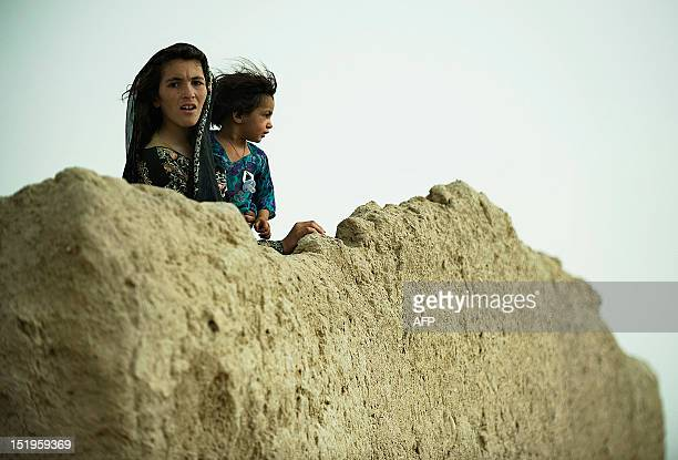 Afghan girls from the local Pashtun tribe stand behind a mud perimeter wall to watch US Army soldiers from the 1st Platoon Delta Coy 164 ARS army...