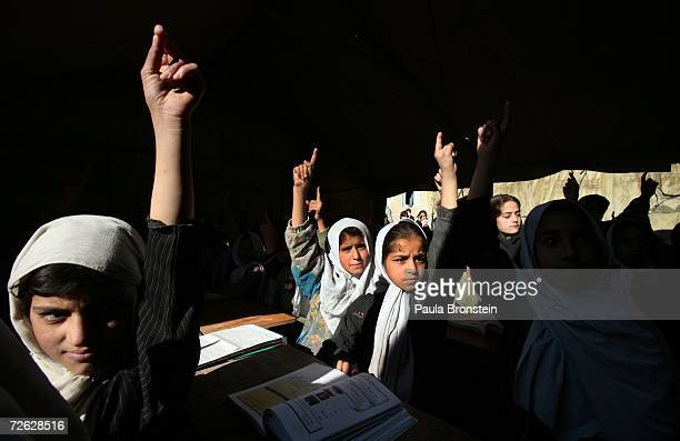 Afghan girls raise their hands during english class at the Bibi Mahroo high school in Kabul Afghanistan November 22 2006 The overcrowded school is...
