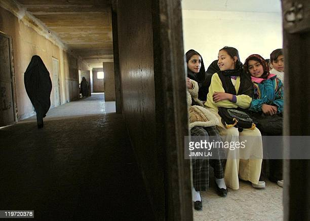 Afghan girls sit inside a classroom while a teacher wearing a burka walks on a corridor on the first day of winter classes at the AlfatHa school in...