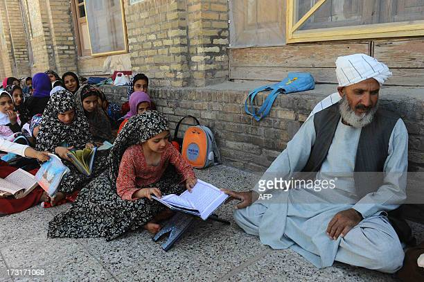 Afghan girls sit on the ground as they study the holy Koran ahead of the Islamic holy month of Ramadan in Herat on July 9 2013 Throughout the month...
