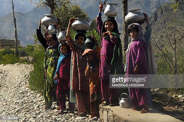 Afghan girls stand as they watch on the road from Shultan to Asad Abad city in Kunar province east of capital Kabul on October 8 2008 About twenty...
