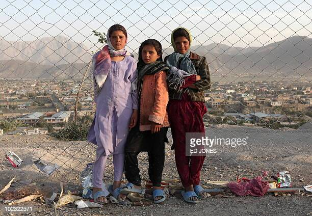Afghan girls stand at a fence as they pose for a photo on a hilltop above Kabul on June 22 2010 US strategy in Afghanistan is being undermined...
