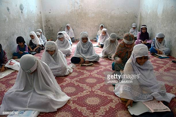 Afghan girls study the Koran at a Madrassa during the month of Ramadan in Kandahar on June 9 2014 Throughout the month devout Muslims must abstain...