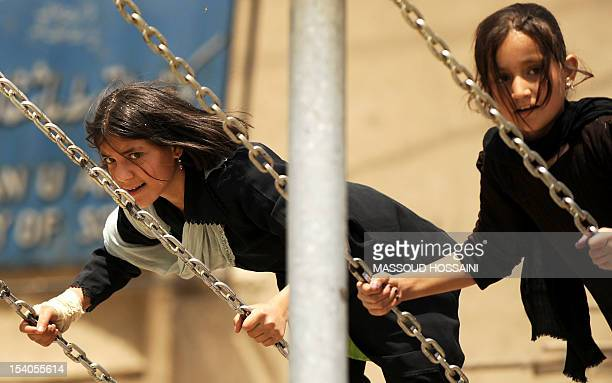 Afghan girls swing in the old part of Kabul on May 23, 2008. Civil war in the Central Asian nation, which followed the Afghan defeat of Soviet...