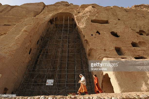 Afghan girls walk past the empty seat of the Buddha destroyed by the Taliban in Bamiyan on July 6 2008 The cavemonasteries of Bamiyan and the niche...