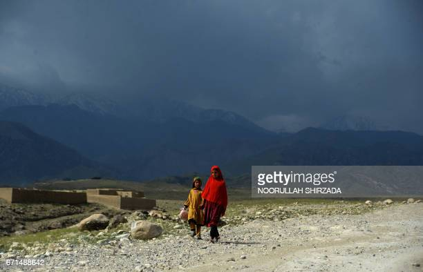 Afghan girls walk through a village near the site of a bomb attack by US forces in the Achin district of Nangarhar province on April 22, 2017. Afghan...