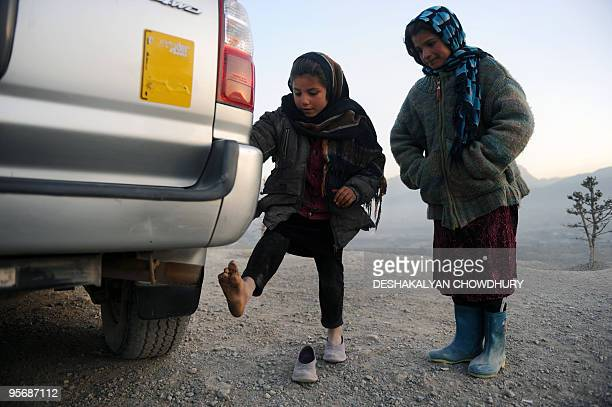 Afghan girls warm their feet over the exhaust of a car's tailpipe in Kabul on January 10 2010 As winter sets in across Central Asia many Afghans...