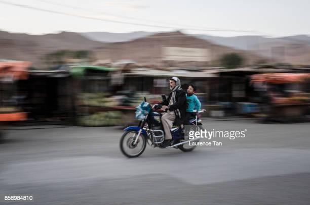 Afghan Hazara commute on a motorcycle along the Bamiyan bazaar on August 8 2017 in Bamiyan Afghanistan Located in central Afghanistan Bamiyan is...