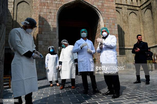 Afghan health services staff wearing protective gear, as a preventive measure against the spread of the COVID-19 coronavirus, wait to check the body...