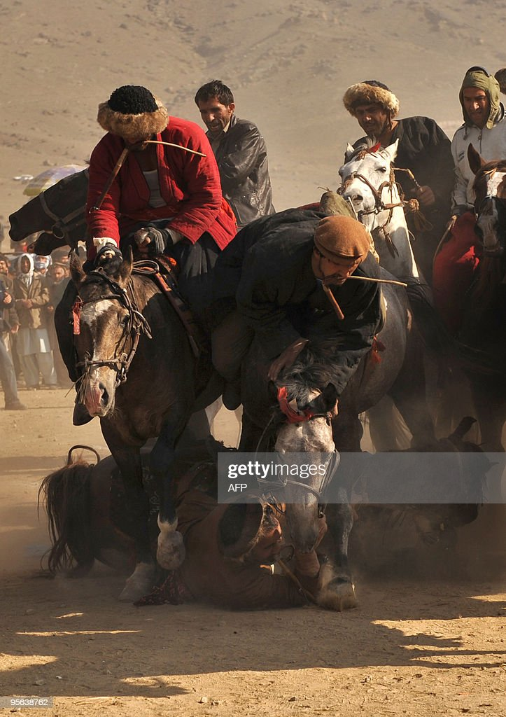 Afghan horsemen compete for the goat carcass as a horsman falls with