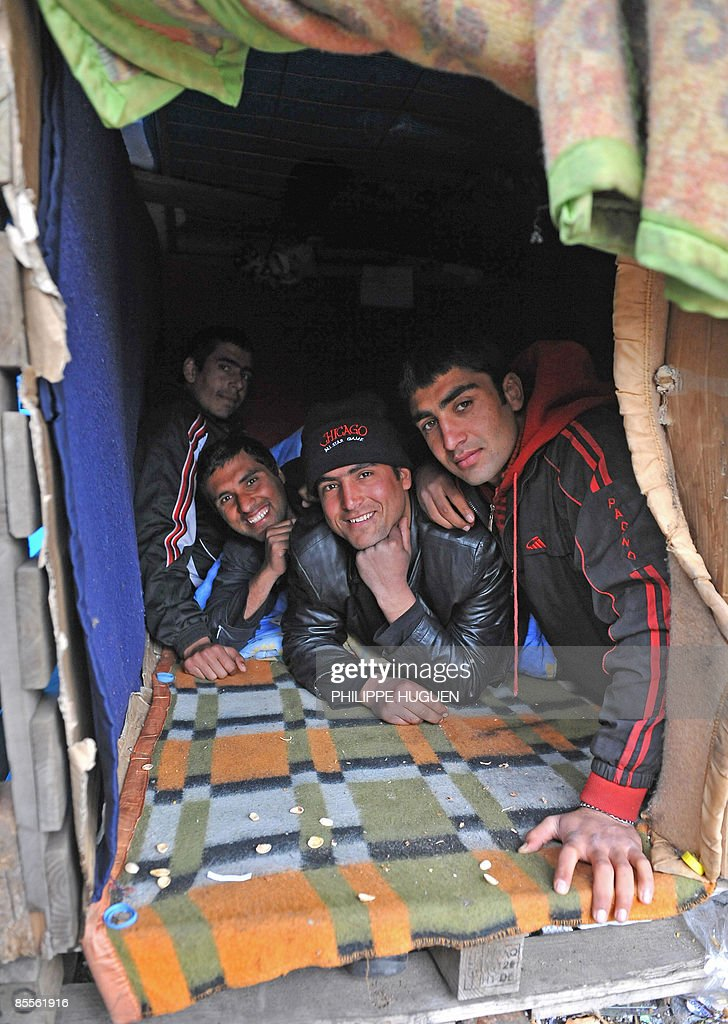 Afghan immigrants protect themselves from coldness in a shelter in a camp named 'Jungle' in the northern city of Calais on March 23, 2009. Calais became a destination for migrants from across the world in the late 1990s with the opening of the Sangatte refugee camp. The camp was finally closed in 2002 but migrants still come to Calais.