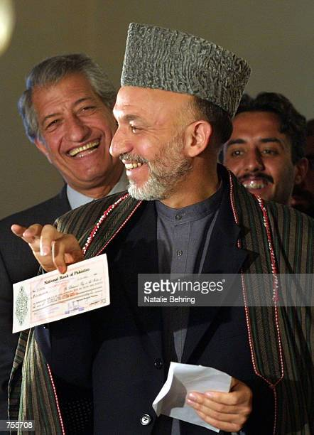 Afghan Interim leader Hamid Karzai smiles as he shows off a 10 million US dollar check presented to him by Pakistani President Pervez Musharraf April...