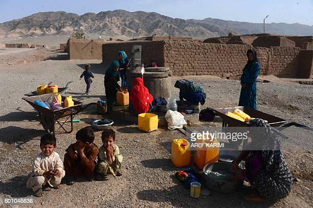 Afghan internallydisplaced women wash clothes outside their temporary house on the outskirts of Herat on September 9 2016 / AFP / AREF KARIMI