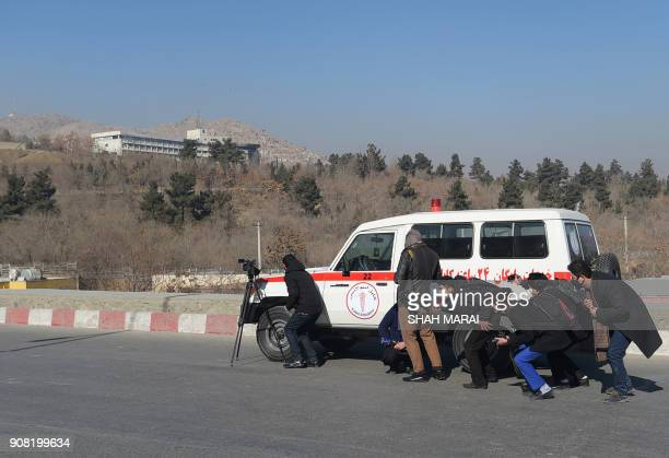 TOPSHOT Afghan journalists take cover behind an ambulance near the Intercontinental Hotel during a fight between gunmen and Afghan security forces in...