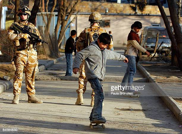 Afghan kids skateboard near their homes along side British ISAF soldiers on patrol on February 02 2009 in Kabul Afghanistan After decades of war many...