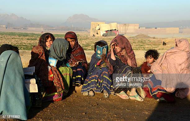 Afghan Kochi nomad girls study outside their tent in the Zhari district of Kandahar province AFP PHOTO / JAVED TANVEER / AFP / JAVED TANVEER
