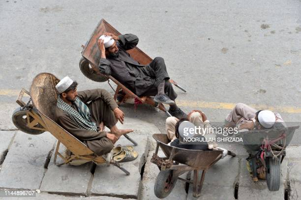 Afghan labourers rest in their wheelbarrows on a street during the holy month of Ramadan in Jalalabad on May 19, 2019. - Muslims throughout the world...