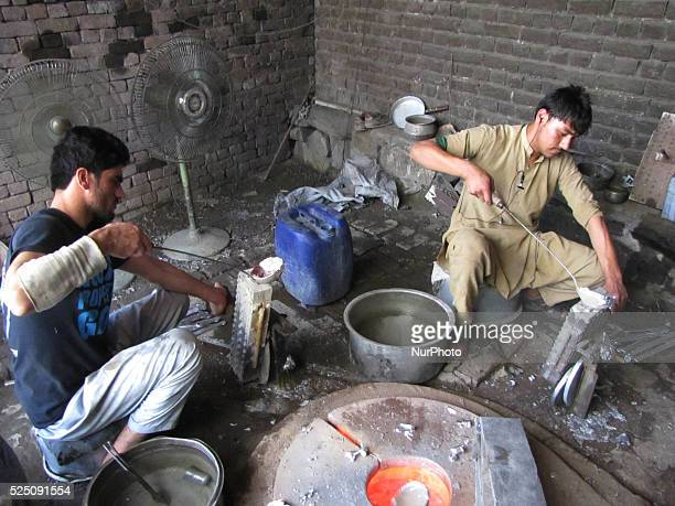 Afghan labourers works at an aluminium on the outskirts of Jalalabad on october 20 2014