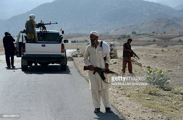 Afghan Local Police keep watch along the road near a checkpoint set alight by Islamic fighters during overnight clashes between Afghan forces and...