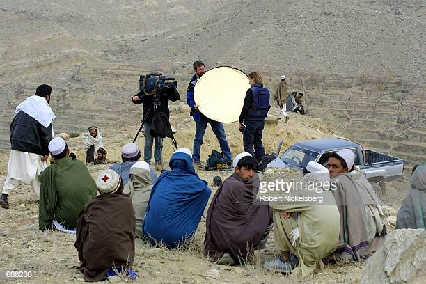 Afghan locals watch as BBC reporter Hillary Anderson films a standup December 16 2001 near Tora Bora Afghanistan