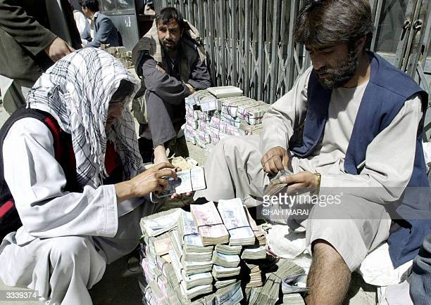 Afghan man Ashmat exchanges Pakistani rupees for Afghanis with money changer Ghani at the exchange market in Kabul 07 April 2004 Despite the country...