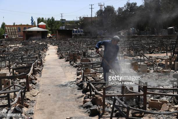 Afghan man shovels off debris after Taliban burned a market in the city of Ghazni on August 14 2018 Afghan forces appeared to have finally pushed...