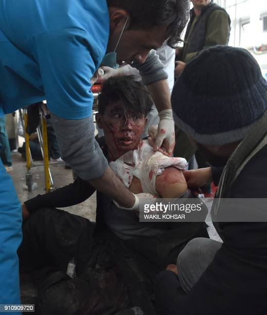 Afghan medical staff treat a wounded boy after a car bomb exploded near the old Interior Ministry building at Jamhuriat Hospital in Kabul on January...