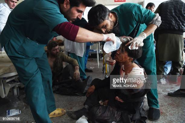 Afghan medical staff treat a wounded man after a car bomb exploded near the old Interior Ministry building at Jamhuriat Hospital in Kabul on January...