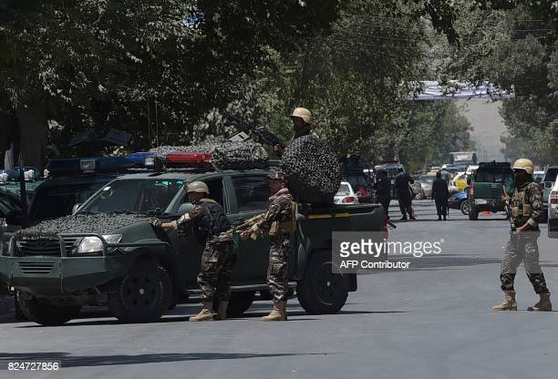 Afghan members of the National Directorate of Security keep watch at the site of a suicide blast near Iraq's embassy in Kabul on July 31 2017 A...