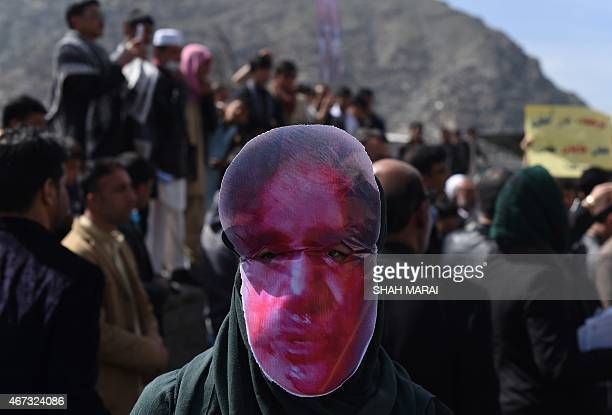 Afghan members of the Solidarity Party of Afghanistan wear masks bearing an impression of the bloodied face of a woman who was lynched by a mob...