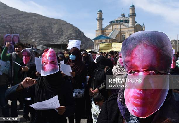 Afghan members of the Solidarity Party of Afghanistan wearing masks bearing an impression of the bloodied face of a woman who was lynched by a mob...