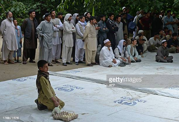 Afghan men and children watch a performance from the Mobile Mini Circus for Children during a show in Paghman district on the outskirts of Kabul on...
