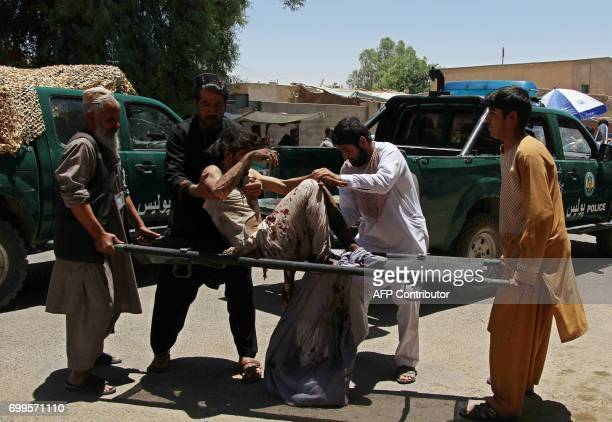 Afghan men carry a victim of a powerful car bomb in Lashkar Gah the capital of Helmand province on June 22 2017 Twenty people were killed June 22...