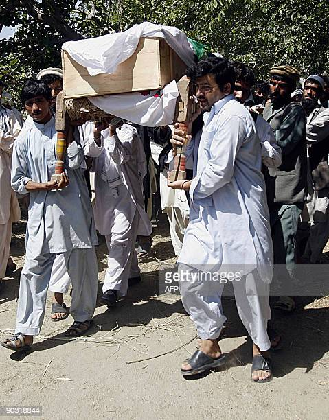 Afghan men carry the body of a civilian suicide attack casualty for burial in Mihtarlam Laghman province on September 3 2009 The Afghan government...