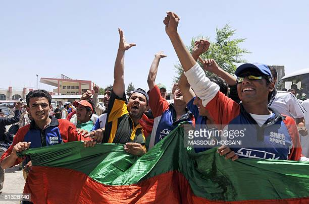 Afghan men celebrate as they welcome the Afghanistan cricket team upon their return to the country following their qualification for the ICC World...