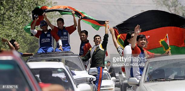 Afghan men celebrate holding national flags as they welcome the Afghanistan cricket team upon their return to the country following their...