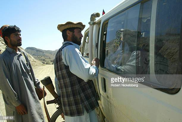 Afghan men check an Afghan vehicle exiting to the Pakistani border town of Ghulam Khan March 27 2002 at the last check post along the AfghanPakistani...