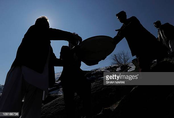 Afghan men distribute food for poor people during celebrations marking the birth anniversary of The Prophet Mohammed at a shrine in Kabul on February...